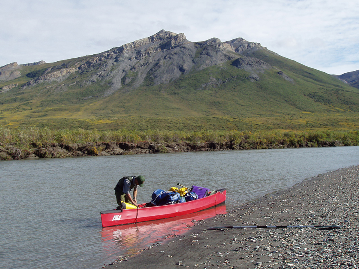 A man stands in a red canoe floating near a rocky river shore.  A mountain dominates the scene.